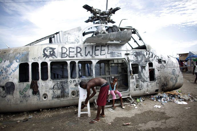 An earthquake survivor washes his hands in a bucket near a damaged helicopter in a provisional camp in downtown Port-au-Prince